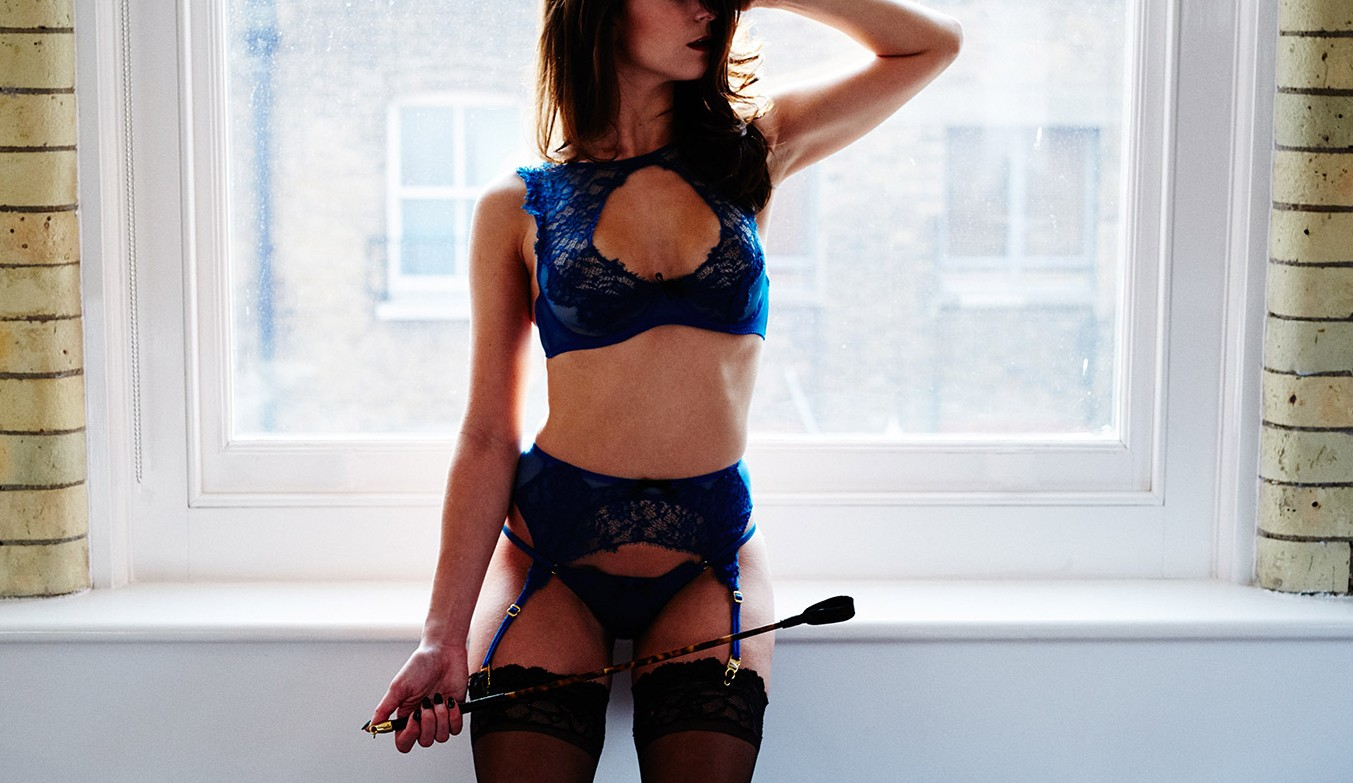 BDSM escort Louisa Knight in lingerie with riding crop