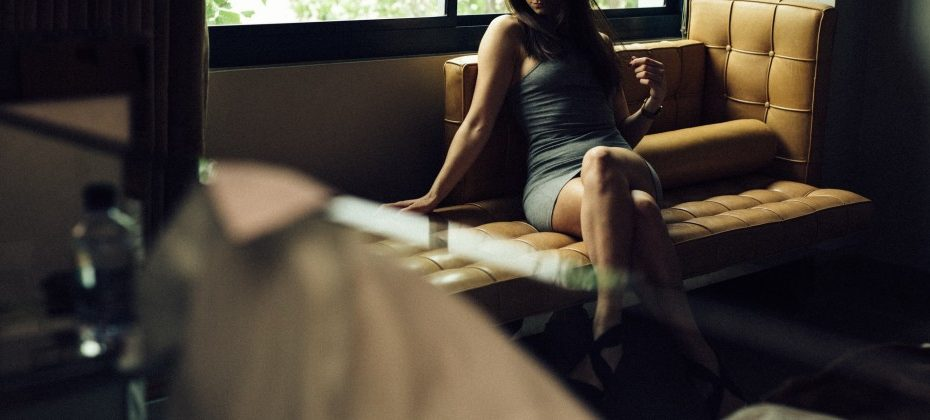 Kinky escort Louisa Knight reclined on a sofa in a tight grey mini dress during international travel
