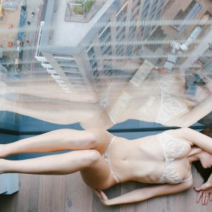 kinky London escort Louisa Knight poses in the window wearing soft cream lingerie