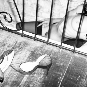 Kinky London escort and submissive Louisa Knight reclines naked on the stairs, wearing only stockings